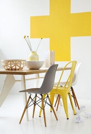 Keltainen seinämaalaus ja tolix-tuoli